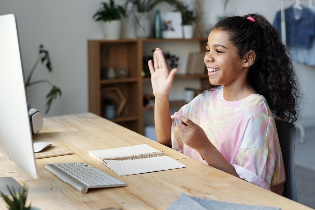 Female student waving to teacher via video-teleconferencing